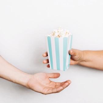 Hände geben popcorn