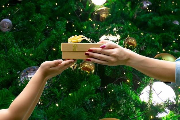Hände geben sie einen geschenkglückwunsch danken ihnen grünen hintergrund