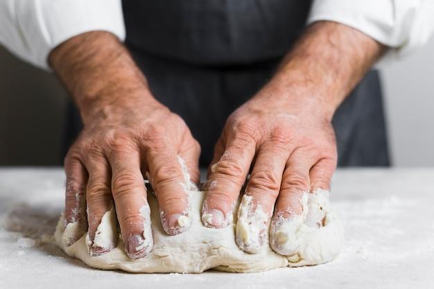 Hände gefüllt mit teig für brot