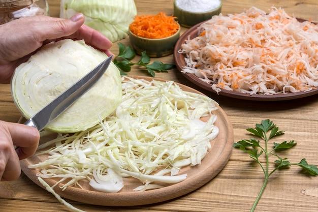 Hände gehackten frischen kohl. sauerkraut in teller, roher kohl, salz und karotten hautnah. gesunde winterernährung. fermentationsprodukte.