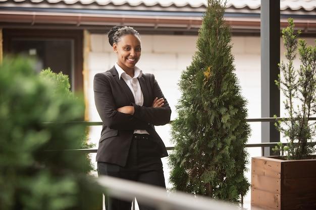 Hände gekreuzt. afroamerikanische geschäftsfrau in bürokleidung lächelnd, sieht selbstbewusst glücklich, beschäftigt aus. konzept für finanzen, wirtschaft, gleichstellung und menschenrechte. schönes junges modell, erfolgreich.