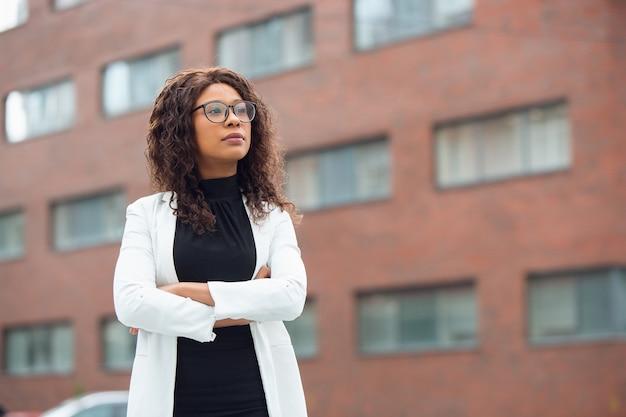 Hände gekreuzt. afroamerikanische geschäftsfrau in bürokleidung lächelnd, sieht selbstbewusst und ernst aus, beschäftigt. konzept für finanzen, wirtschaft, gleichstellung und menschenrechte. schönes junges modell, erfolgreich.