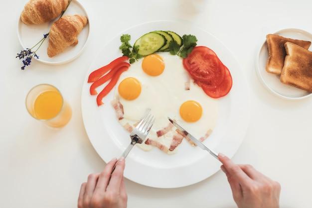 Hände geschnittenes frühstück auf dem tisch ist saft und croissant.