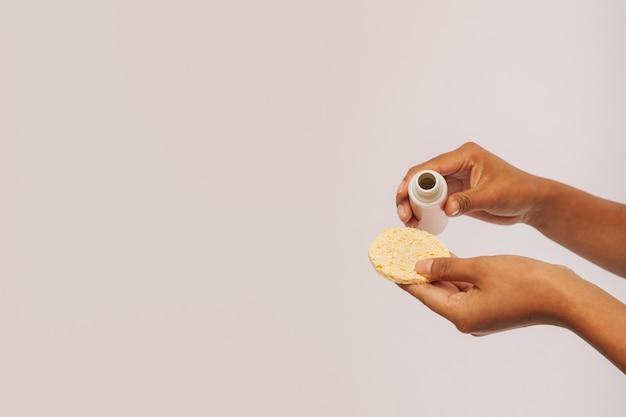 Hände gießen lotion auf einem wattepad
