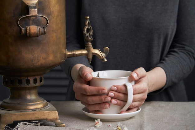 Hände gießen tasse tee von vintage samowar