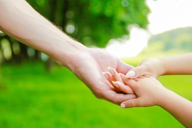 Hände glückliche eltern und kind draußen im park