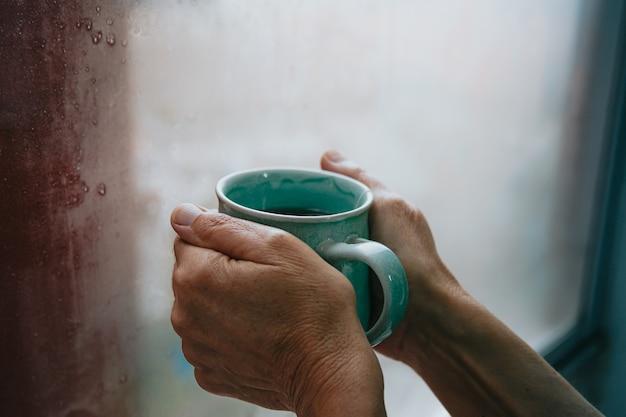 Hände greifen an einem kalten tag nach einem schnellen tee