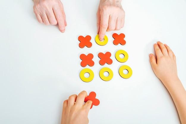 Hände großmutter und enkel spielen tic-tac-toe-holz-brettspiel
