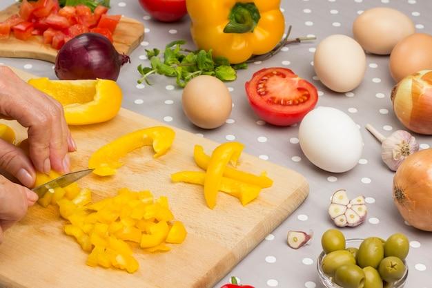 Hände hacken gelben pfeffer auf schneidebrett. eier, oliven, knoblauchtomaten auf dem tisch