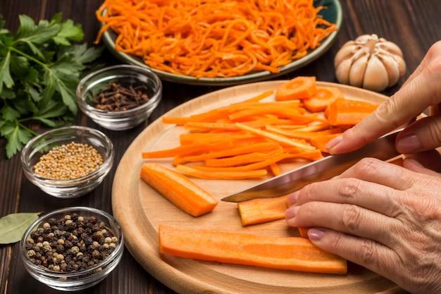 Hände hacken rohe karotten auf schneidebrett. gewürze, knoblauch und petersilie auf dem tisch. fermentierte karotten in platte. natürliches erkältungsmittel. nahansicht.