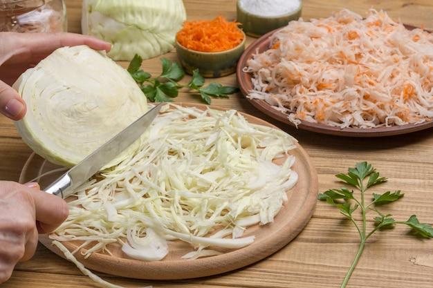 Hände hacken rohkohl in scheiben schneiden, halber kohlkopf. sauerkraut in teller. hausgemachte fermentationsprodukte. nahansicht