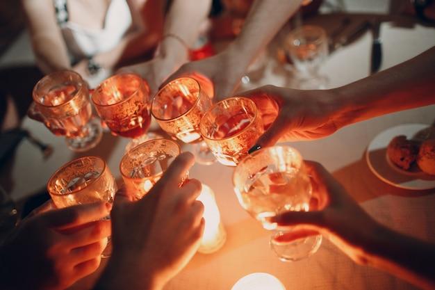 Hände halten die gläser mit getränk, das einen toast auf der party macht. weichzeichner und brennende kerze im hintergrund