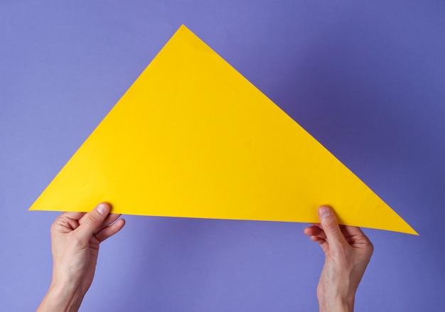 Hände halten ein gelbes dreieck auf einem lila