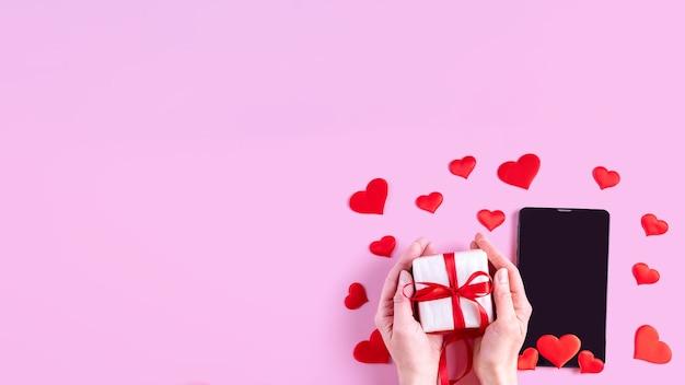Hände halten ein geschenk mit einem roten band über einem schwarzen leeren bildschirm eines tablets oder telefons mit roter herzform