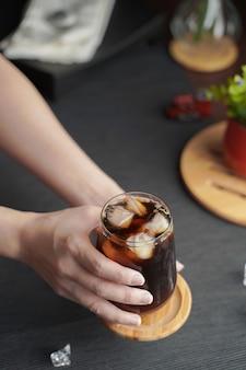 Hände halten ein glas espresso mit zitronensaft und frisch geschnittener zitrone auf holztisch und kopierraum, sommercocktail, kalt gebrühten kaffee oder schwarzen tee. (nahaufnahme, selektiver fokus)