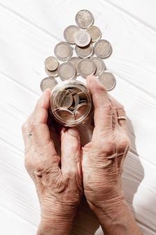 Hände halten ein glas mit münzen draufsicht gefüllt