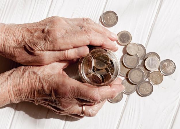Hände halten ein glas mit münzen gefüllt