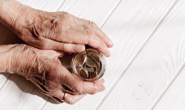 Hände halten ein glas münzen