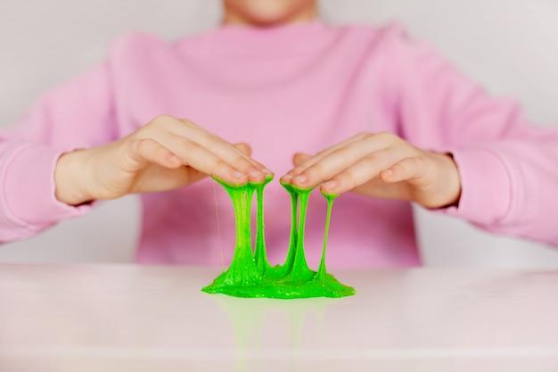 Hände halten ein hausgemachtes spielzeug namens schleim