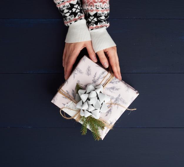 Hände halten ein papier geschlossenes geschenk