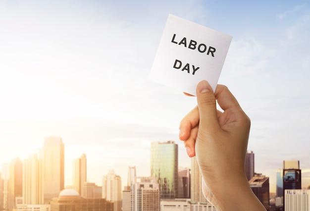 Hände halten ein papier mit labor day nachricht