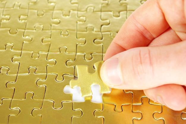 Hände halten ein puzzleteil. geschäftskonzepte