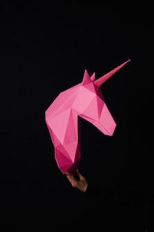 Hände halten ein rosa einhorn. kunstwerk. papiermodell 3d eines einhorns. kopieren sie platz