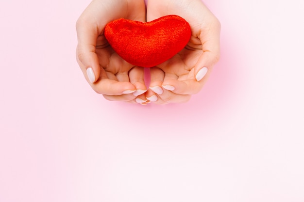 Hände halten ein zartes rotes plüschherz auf einem rosa hintergrund mit unterem leerraum für werbung.