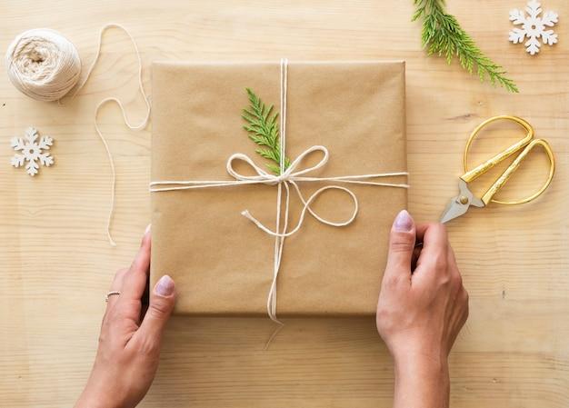 Hände halten eine geschenkbox. draufsicht, die geschenkkonzept herstellt