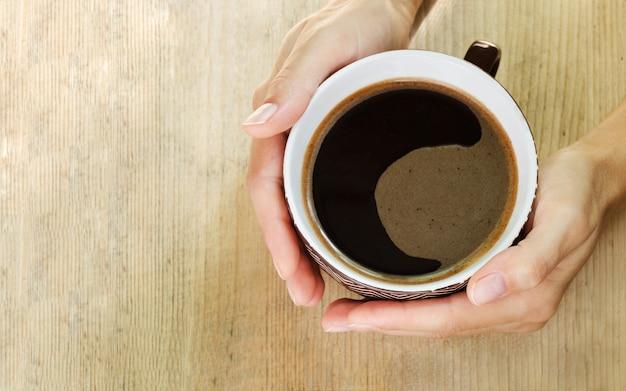 Hände halten eine große tasse kaffee. ansicht von oben.