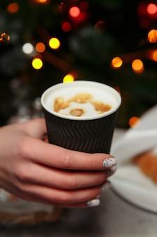 Hände halten eine heiße tasse kaffee. kaffee zum mitnehmen im winter.