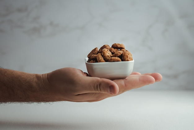 Hände halten eine keramikschale gefüllt mit schokoladenkeksen auf einer kunstvollen weißen wand. minimalistisches lebensmittelfoto