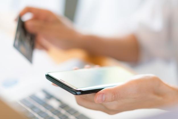 Hände halten eine kreditkarte mit laptop-computer und handy für online-shopping