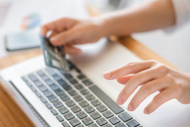 Hände halten eine kreditkarte und mit laptop-computer für online-shopping