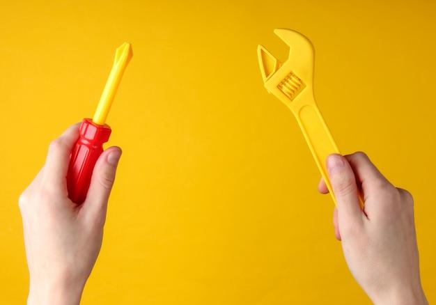 Hände halten einen spielzeugschraubendreher und schraubenschlüssel auf einer gelben oberfläche