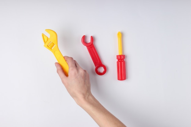 Hände halten einen spielzeugschraubendreher und schraubenschlüssel auf weißer oberfläche