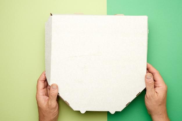 Hände halten einen weißen karton