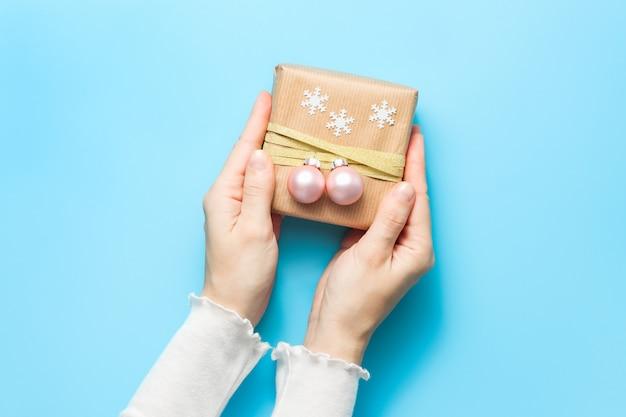 Hände halten geschenkbox mit weihnachtskugeln und schneeflocken verziert
