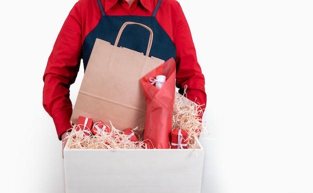 Hände halten geschenke, packtasche und flasche wein