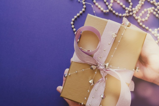 Hände halten goldene geschenkbox mit glitzernden rosa band festlichen feiertagen weihnachten neujahrshintergrund