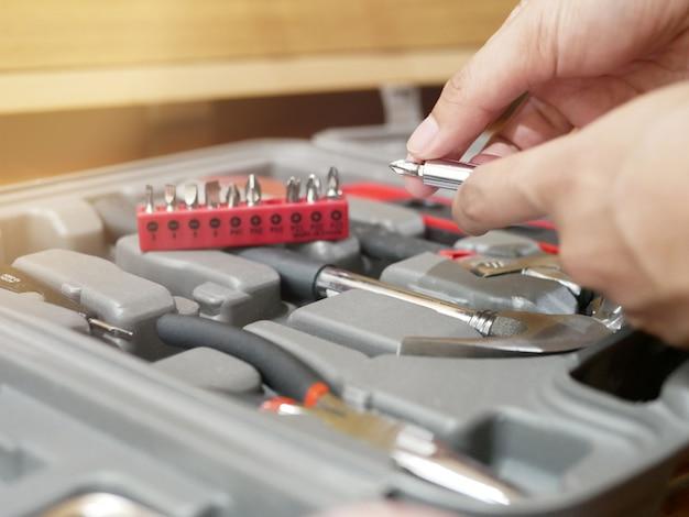 Hände halten griffe, drehen köpfe des schraubendrehers und wechseln köpfe in verschiedenen größen im werkzeugkasten.