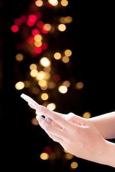 Hände halten handy auf weihnachten hintergrund. festlich eleganten hintergrund mit bokeh lichter und sterne, kopieren raum
