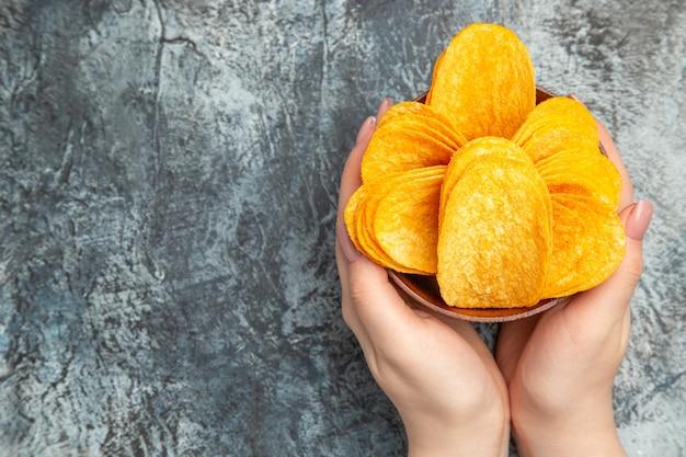 Hände halten hausgemachte köstliche knusprige pommes in einer braunen schüssel auf der linken seite des grauen tisches