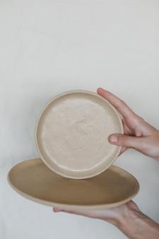 Hände halten keramikplatten isoliert auf weißem hintergrund minimalistisches set von handgefertigten keramik-tisch...