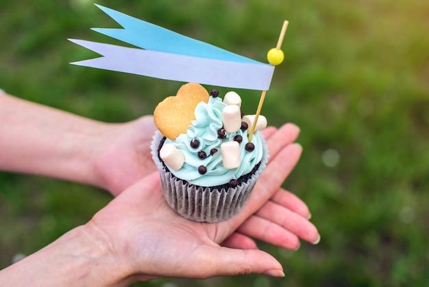 Hände halten köstlichen cupcake mit blauer sahne und marshmallows