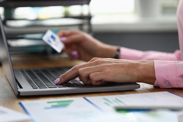 Hände halten kreditkarte und geben informationen in laptop ein
