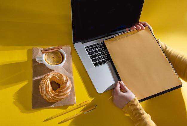 Hände halten lebenslauf in der nähe von laptop, kuchen und tasse tee