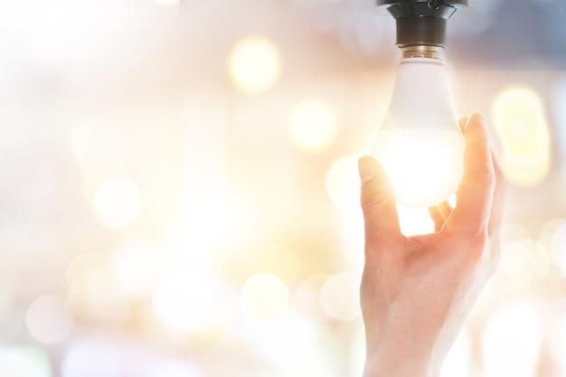 Hände halten leuchtende glühbirnen
