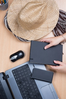 Hände halten notizbuch mit laptop und hut
