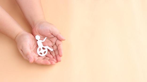 Hände halten papierausschnitt person, die im rollstuhl sitzt